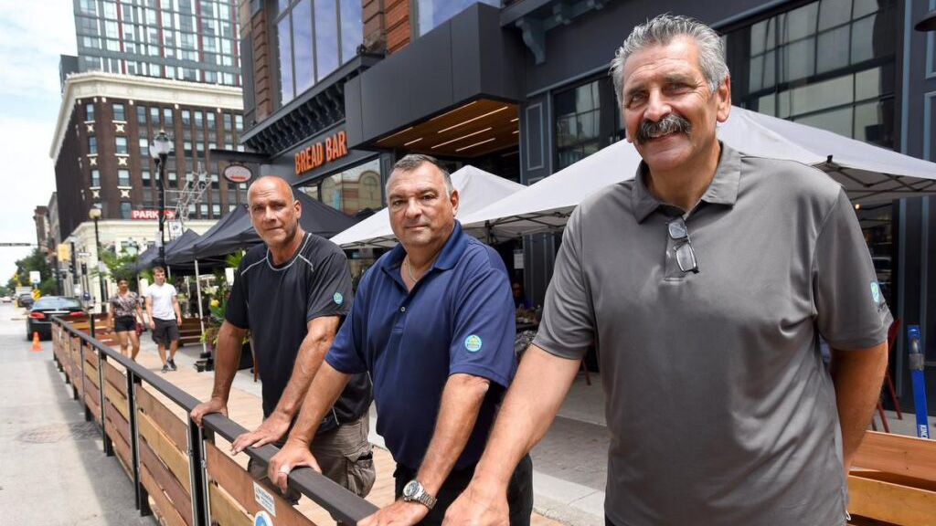 Carlo Rullo, Saverio Valerio and Mike Raso behind a street patio