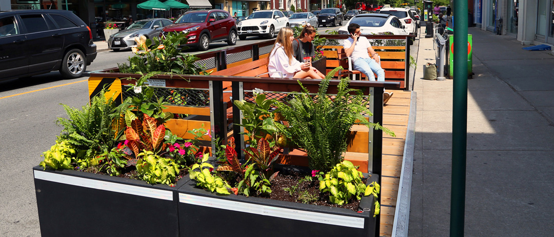 planter box example with flowers surrounding a street patio that are low