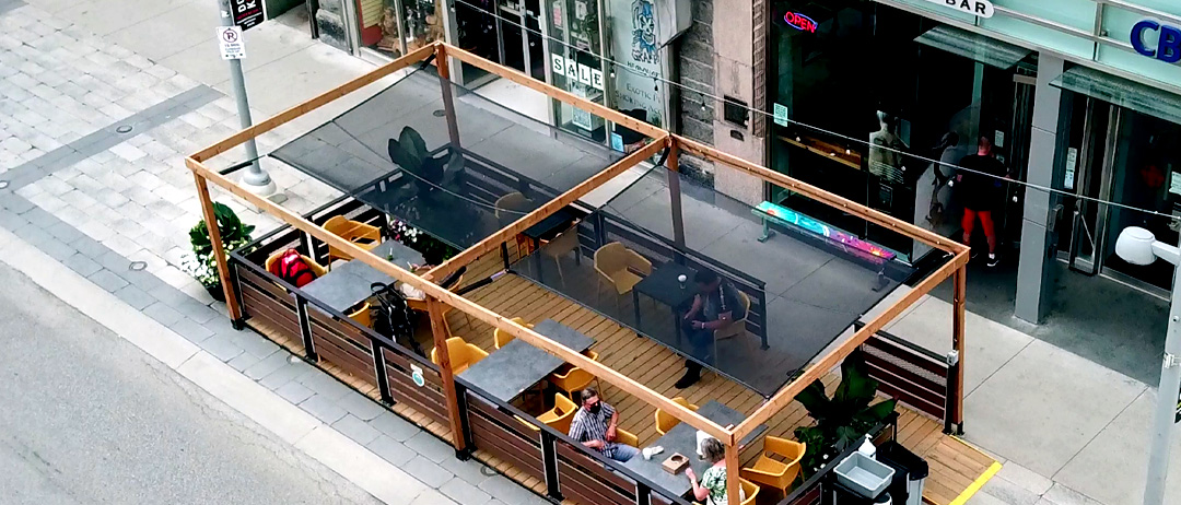 sunshade example with high wooden frames and mesh canopies over a street patio